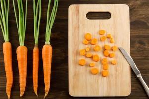 bouquet de carottes fraîches avec des feuilles vertes sur bois