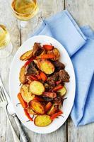 viande rôtie avec pommes de terre, carottes, oignons, romarin et ail photo