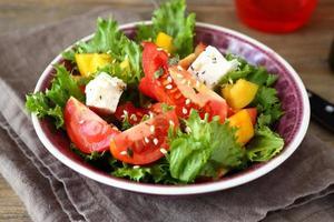 salade de tomates, fromage et légumes verts photo