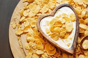 petit-déjeuner sain: cornflakes avec du lait dans un bol en bois photo