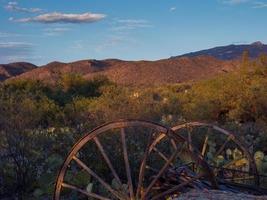 Roues de chariot rouillé dans le désert de l'Arizona au coucher du soleil photo