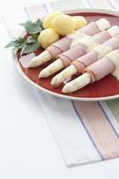 asperges, pommes de terre, jambon et persil en plaque sur fond blanc photo