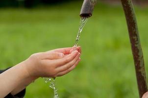 mains d'enfants avec de l'eau claire et propre photo