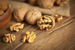 cerneaux de noix et noix entières sur une vieille table en bois rustique photo