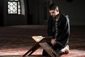 jeune homme musulman lisant le coran photo