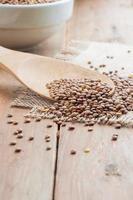 Lentilles biologiques avec faux en bois sur fond de toile de jute photo