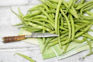 Haricots verts crus (Phaseolus vulgaris) couteau antique sur une serviette en tissu photo