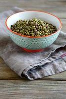 haricot mungo dans un bol sur une serviette en lin, fond en bois photo