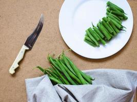 haricots verts tranchés sur plaque blanche et un bouquet photo