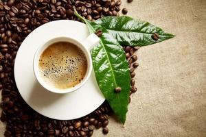 tasse à café en mousse, grains à gauche, feuilles vertes sur lin photo