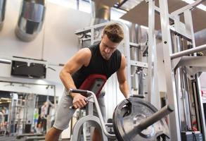 jeune homme, exercisme, sur, barre t, machine rang, dans, gymnase photo