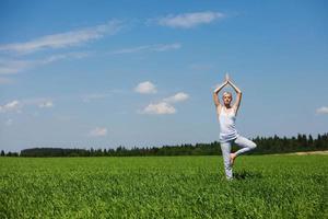 belle jeune femme en bonne santé, faire des exercices d'yoga sur l'herbe verte. photo