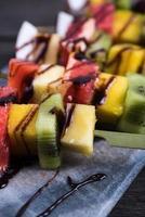 collation saine, fruits exotiques sur des brochettes avec trempette au chocolat
