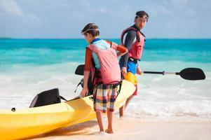 père et fils tirant sur le kayak photo