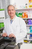 pharmacien senior souriant à l'aide d'ordinateur photo