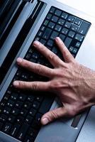 la main sur l'ordinateur portable photo