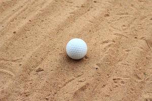 balle de golf sur le sable photo