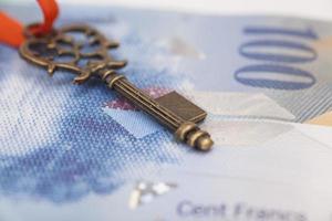 clé du succès avec un arc rouge sur un billet en franc suisse