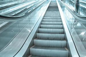 Escalier mécanique en mouvement contemporain à l'intérieur du hall bleu des affaires