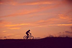 homme, à, vélo montagne, levers de soleil photo
