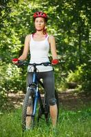 heureuse jeune femme se pencha sur le guidon de son vélo. photo