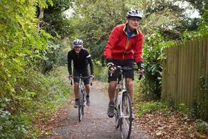 Deux cyclistes mâles matures à vélo le long du chemin photo