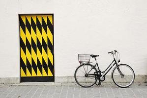 vieux vélo de ville contre un grand mur avec porte photo