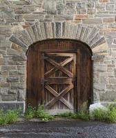 vieille porte en bois dans un mur en pierre de grange photo