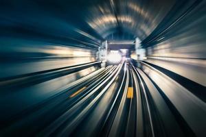 Tunnel de métro avec des pistes lumineuses floues avec train arrivant photo