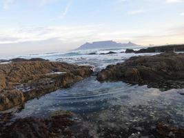 l'eau ondulant à travers les rochers au bord de la mer photo
