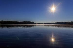 soleil starburst sur lac calme photo