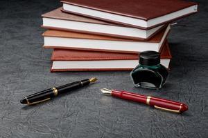 stylos plume avec de l'encre et une pile d'organisateurs photo