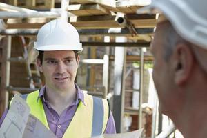 architecte discutant des plans avec le constructeur photo