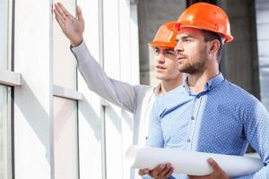 beaux constructeurs discutent du plan de travail photo