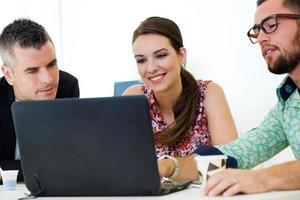 cadres occasionnels travaillant ensemble lors d'une réunion avec un ordinateur portable. photo