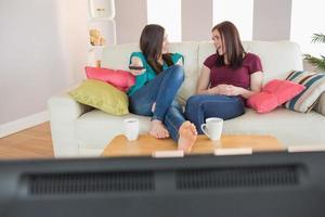 deux amis heureux sur le canapé à regarder la télévision ensemble photo