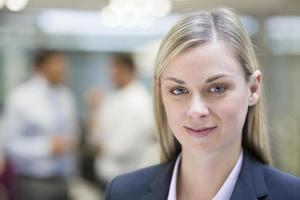 jolie femme d'affaires posant pendant que ses collègues parlent ensemble en arrière-plan