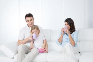 famille prenant son petit déjeuner sur le canapé photo