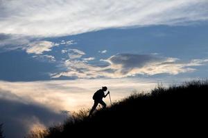 randonneur de montagne devant le coucher du soleil photo