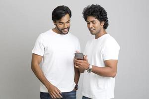 heureux deux jeunes hommes à l'aide de smartphone photo