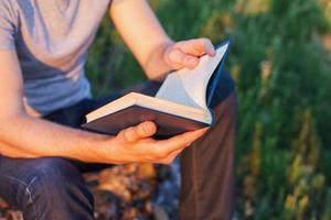 les mains des hommes tiennent le livre ouvert photo