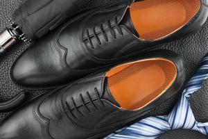 chaussures pour hommes classiques, cravate, parapluie sur le cuir noir photo