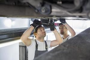 Ingénieurs d'entretien réparant la voiture en atelier photo