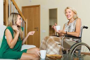 Amie visitant une femme handicapée photo