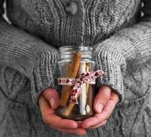 mains féminines tenant des bâtons de cannelle de Noël photo