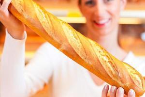femme boulanger dans sa boulangerie avec baguette photo