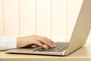 main féminine écrit sur ordinateur portable, gros plan photo