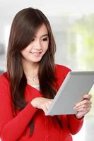 jeune femme en rouge à l'aide de la tablette tactile photo