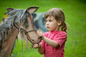 la jeune fille nourrit un cheval en bois photo