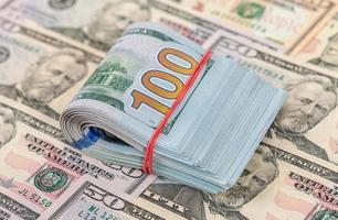 Billets d'un dollar pliés enveloppés de caoutchouc couché sur des billets de banque photo